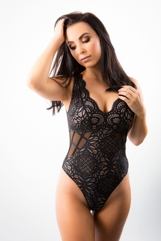 woman in black bodysuit poses for boudoir photos in a Perth studio